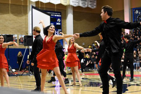 During dance production's performance, advanced dancer, senior Jordyn Apostolache (12) dances with Max Miller (12). Every year at the Winter Pep Rally, dancers pick a partner to dance with for a s上g, even though he may not be involved in dance.